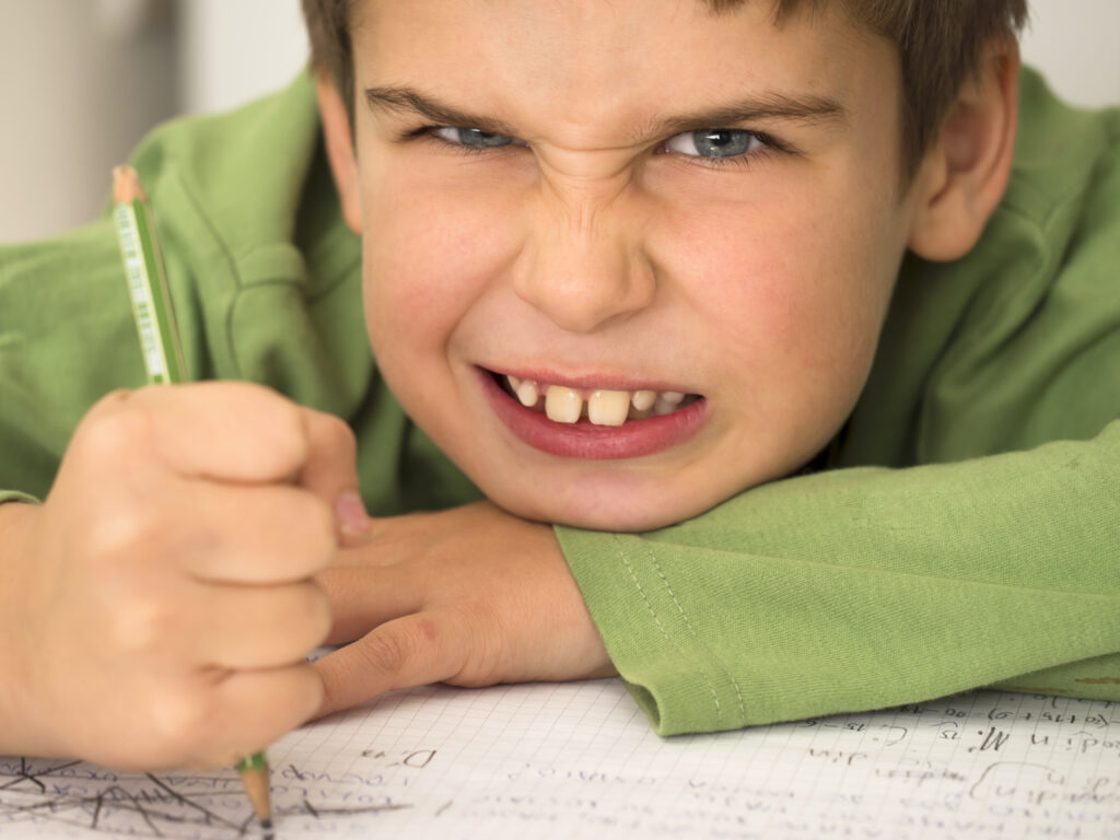 frustrated boy doing homework -writng patch